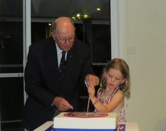 Bill, oldest active sailor, and Tegwyn, youngest at 6, pair up to ceremoniously cut the GLYCs 80th birthday cake