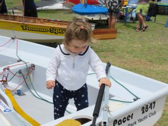 16 month old Laura Taig checks over the rudder on Good Pace.  It's wise to start them young.